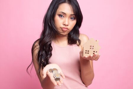 Young asian woman with house model and money coin on pink background