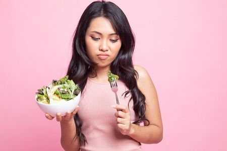 Asian woman hate salad on pink background