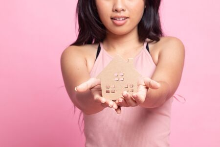 Happy young asian woman with house model on pink background