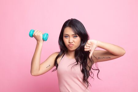 Unhappy Asian woman thumbs down with dumbbells on pink background Banco de Imagens