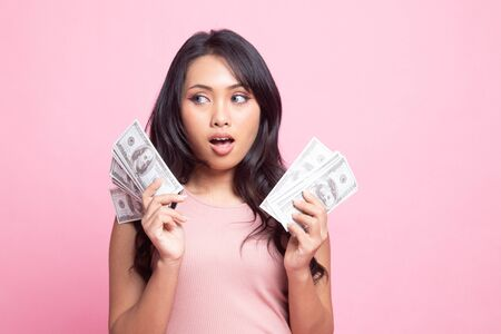 Portrait of  young asian woman  showing bunch of money banknotes on pink background