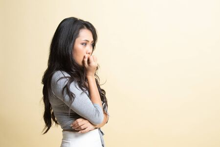 Unsure hesitant nervous young asian  woman biting her fingernails   on beige background
