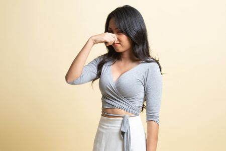 Young Asian woman holding her nose because of a bad smell on beige background Foto de archivo