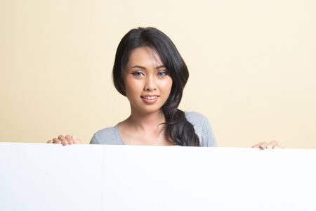 Young Asian woman with blank sign   on beige background