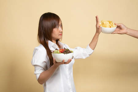 Young Asian woman with salad say no to potato chips on beige background
