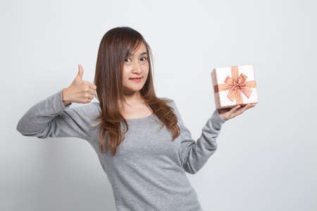 Asian woman thumbs up with a gift box on white background