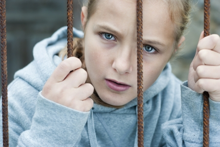 Sad lonely child is behind grid Stock Photo - 16334636