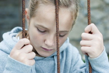 Sad lonely child is behind grid Stock Photo - 16334657