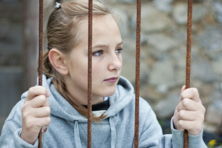 Sad lonely child is behind grid Stock Photo - 16334640