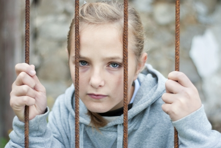 woman prison: Sad lonely child is behind grid Stock Photo