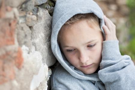 maltrato infantil: Pequeño niño triste con capucha.
