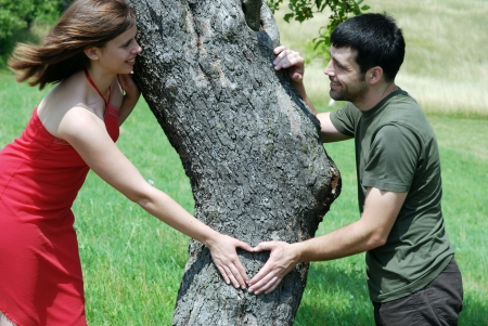 emotional woman: Couple is putting their hands on tree in a shape of heart