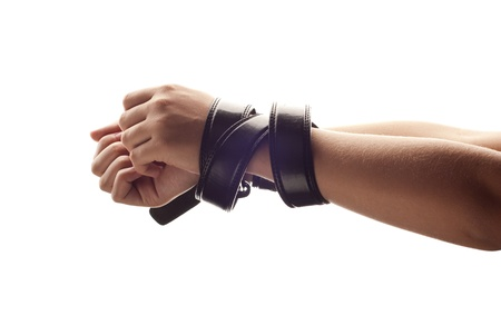 Hands of woman are tied up by belt. photo