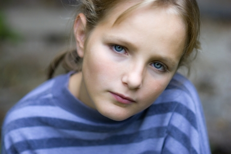 Sad little girl is looking with serious face at camera. photo