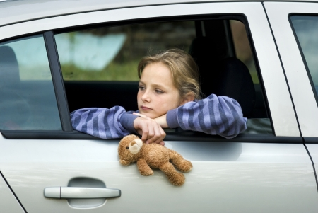 child sad: Little girl in car is going to miss her friends.
