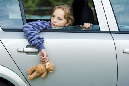 Little girl in car is going to miss her friends  photo