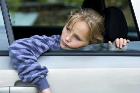 bambini tristi: Bambina in auto sta per perdere i suoi amici Archivio Fotografico