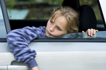 unhappy family: Little girl in car is going to miss her friends