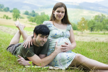 Husband with pregnant wife is resting in nature. photo