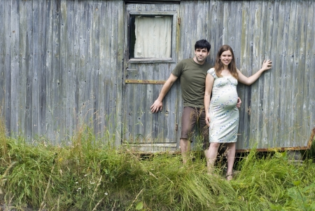 Husband with pregnant wife in front of their old house. photo