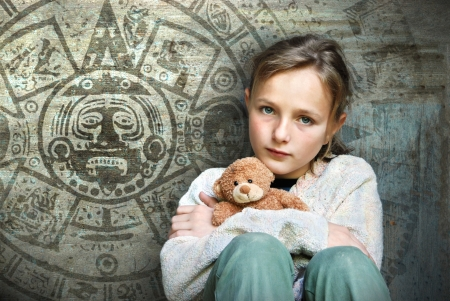 Frightened child with mayan calendar on her background. photo