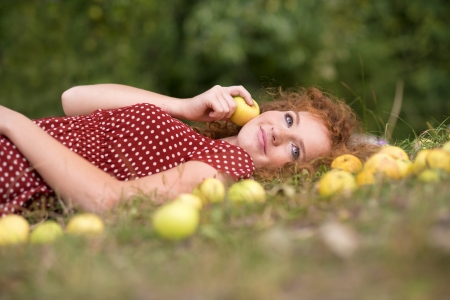 Girl with apple is lying in the garden. photo