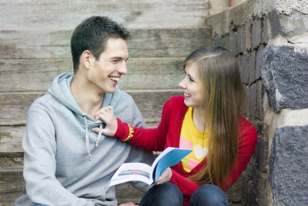 teen couple: Young students are reading book together.