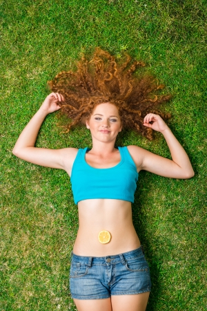 sour grass: Girl with fruit lying on the grass Stock Photo