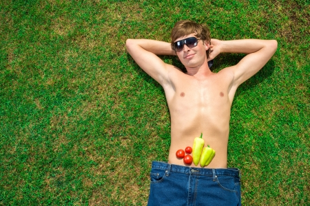sexy food: Man with vegetables is lying on the grass
