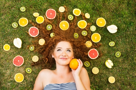Girl with fruit lying on the grass Stock Photo