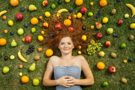 summer diet: Girl with fruit lying on the grass Stock Photo