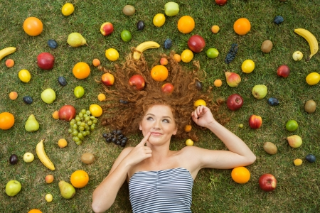 Girl with fruit lying on the grass photo