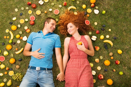 Couple with fruit is lying on the grass photo