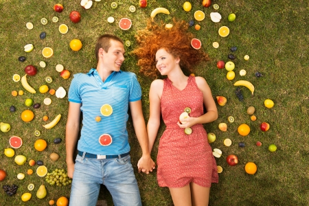 Couple with fruit is lying on the grass Stock Photo - 16436847