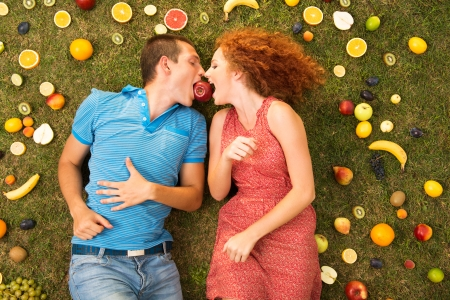 Couple with fruit is lying on the grass Stock Photo - 16436904