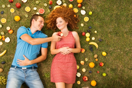 Couple with fruit is lying on the grass Stock Photo - 16436806