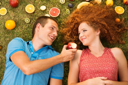 Couple with fruit is lying on the grass Stock Photo - 16436927