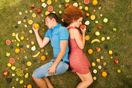 Couple with fruit is lying on the grass Stock Photo - 16436840
