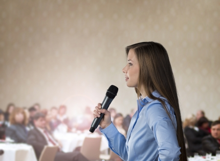 speaker: Beautiful business woman is speaking on conference. Stock Photo