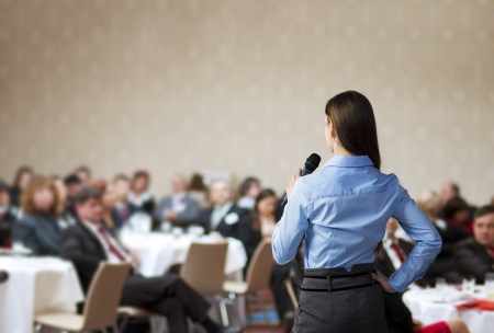 public speaker: Beautiful business woman is speaking on conference. Stock Photo