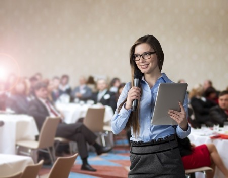 business event: Beautiful business woman is speaking on conference. Stock Photo