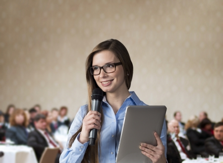 spokesman: Beautiful business woman is speaking on conference. Stock Photo