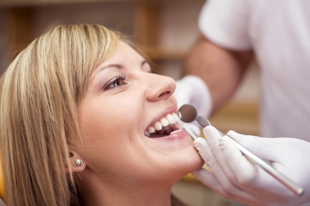 Dentist is doing treatment procedures in dental office. photo