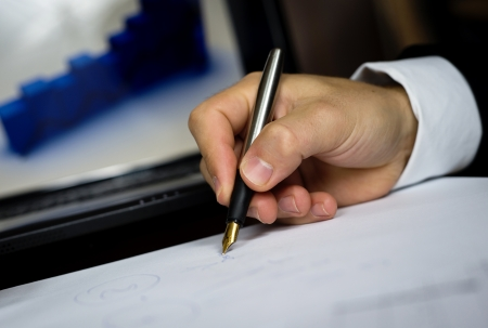 Businessman is writing report on the office desk Stock Photo - 16847189
