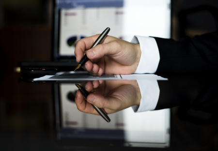 Businessman is signing a document on the office desk Stock Photo - 16847184