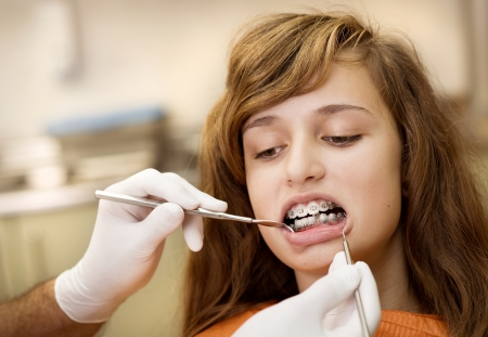 Teenage girl with the braces on her teeth is having a treatment at dentist photo