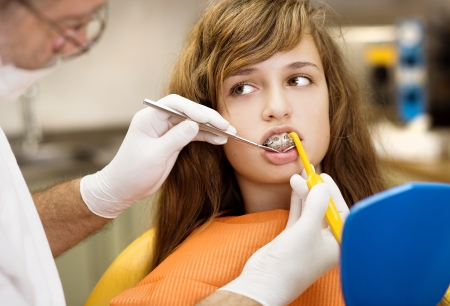 Teenage girl with the braces on her teeth is having a treatment at dentist Stock Photo - 16970667
