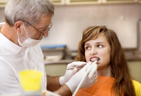 cavity braces: Teenage girl with the braces on her teeth is having a treatment at dentist