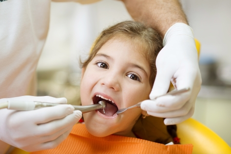 Little girl is having her teeth examined by dentist photo