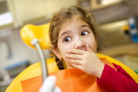 dental fear: Little girl is having her teeth checked by dentist